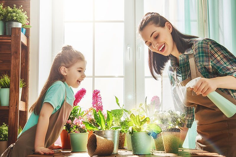 Mother And Daughter Watering Plants