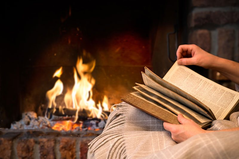 Reading A Book By An Open Fire